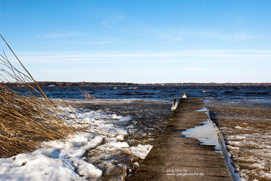 Anlegestelle am Hotel am Zwischenahner Meer. Gefrorene Eisflächen und Schnee am Ufer.