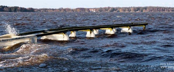 Gefrorene Pfeiler an einer Anlegestelle für kleinere Boote am Zwischenahner Meer in Bad Zwischenahn im winterlichen März 2013
