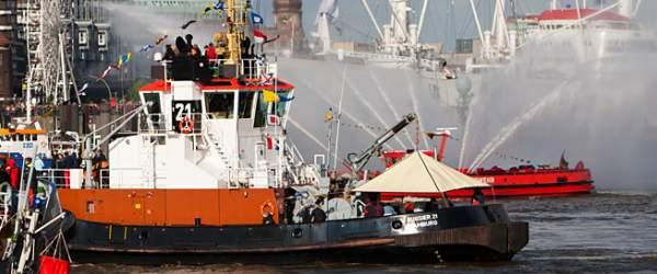 Schlepperballett auf der Elbe vor den Landungsbrücken und im Hintergrund das rote Feuerwehr-Löschboot mit Wasserfontänen.