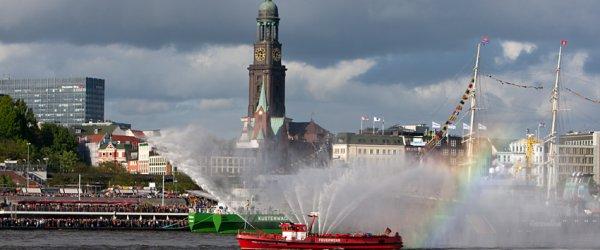 Feuerwehr-Löschboot mit Hamburger Wahrzeichen (Michel) im Hintergrund.